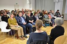 Das Foto zeigt die Teilnehmerinnen und Teilnehmer der Veranstaltung. Im Vordergrund sind zwei Gebärdendolmetscherin zu sehen. Sie sitzen zum Publikum hingewandt.